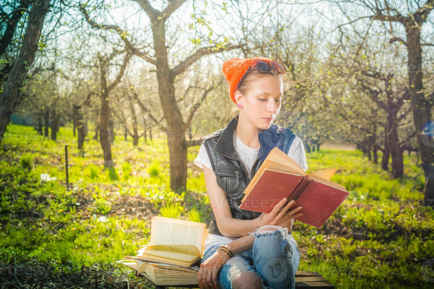 Frau im Park im Freien mit Tablette und Buch entscheiden, was foto