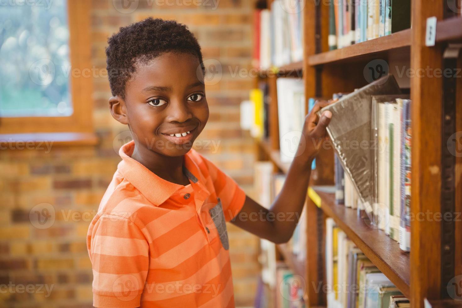 Porträt des Jungen, der Buch in der Bibliothek auswählt foto