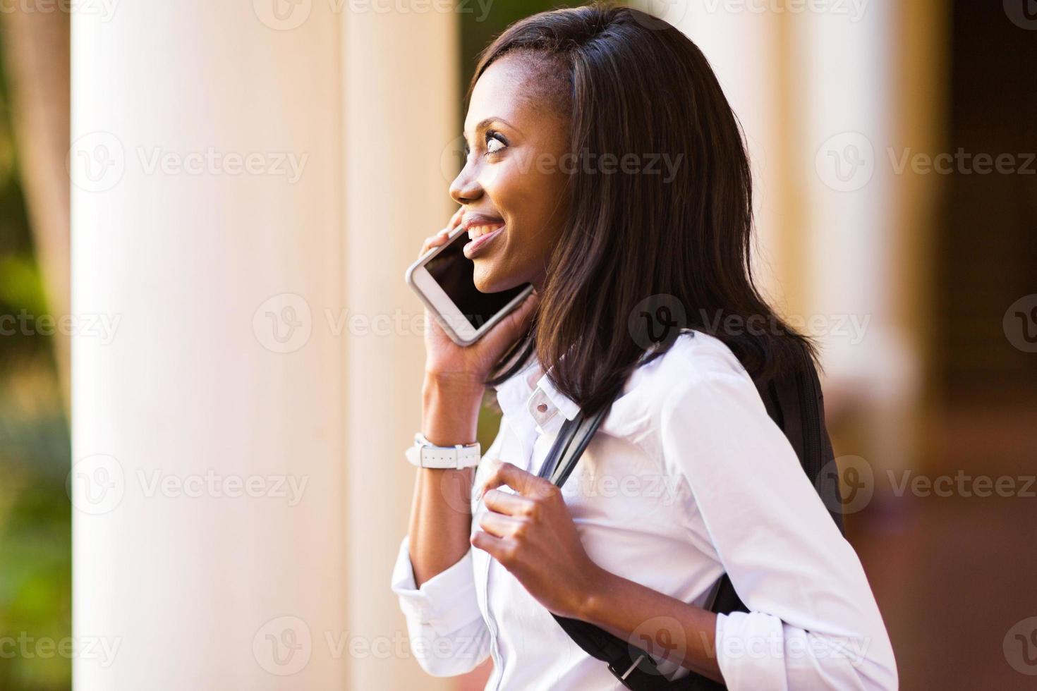 Afroamerikaner College-Student, der einen Anruf macht foto