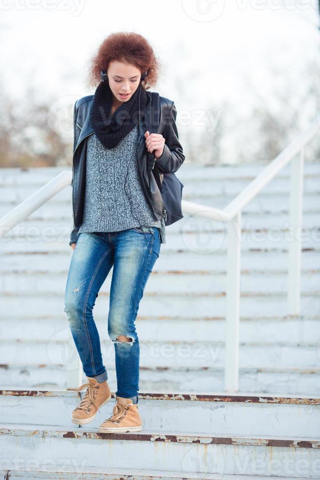 Frau mit dem lockigen Haar, das im Freien die Treppe hinuntergeht foto