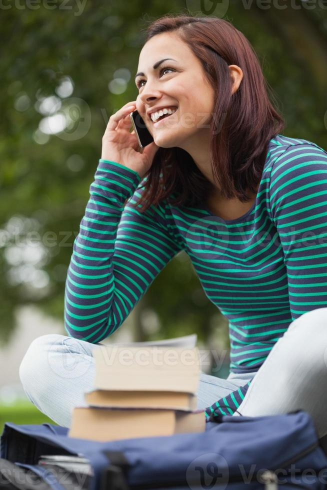 fröhlicher lässiger Student, der auf Bank sitzt und anruft foto