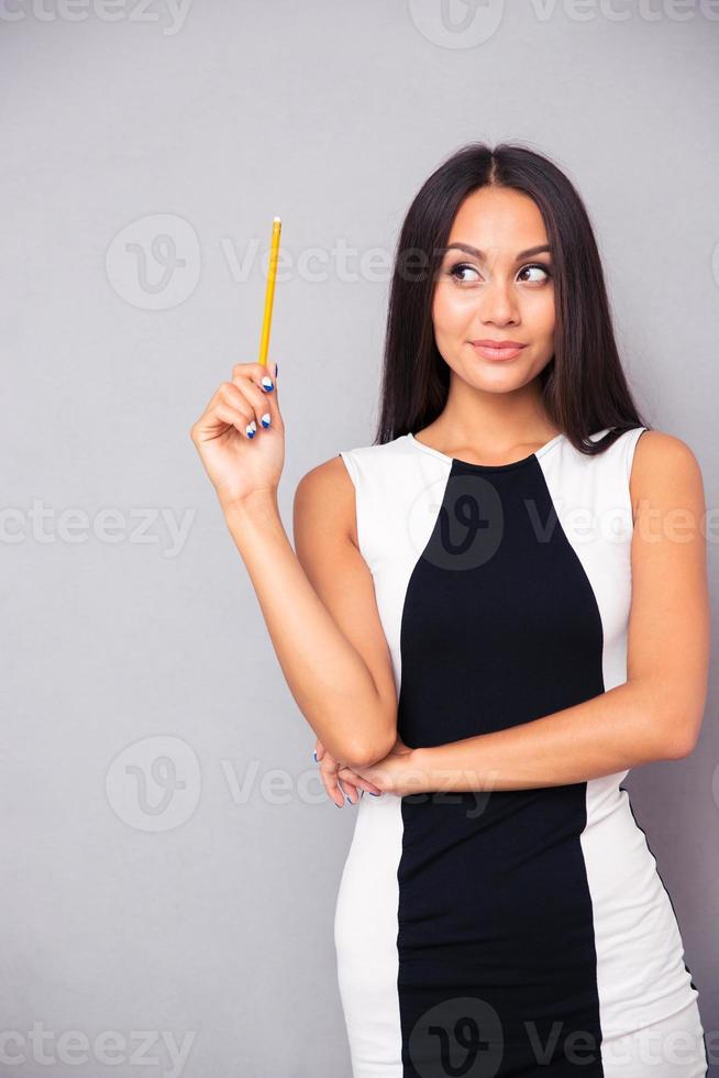 Porträt einer nachdenklichen Frau, die Bleistift hält foto