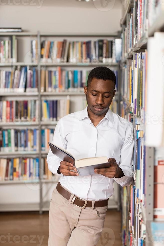 männlicher Student in einer Bibliothek foto