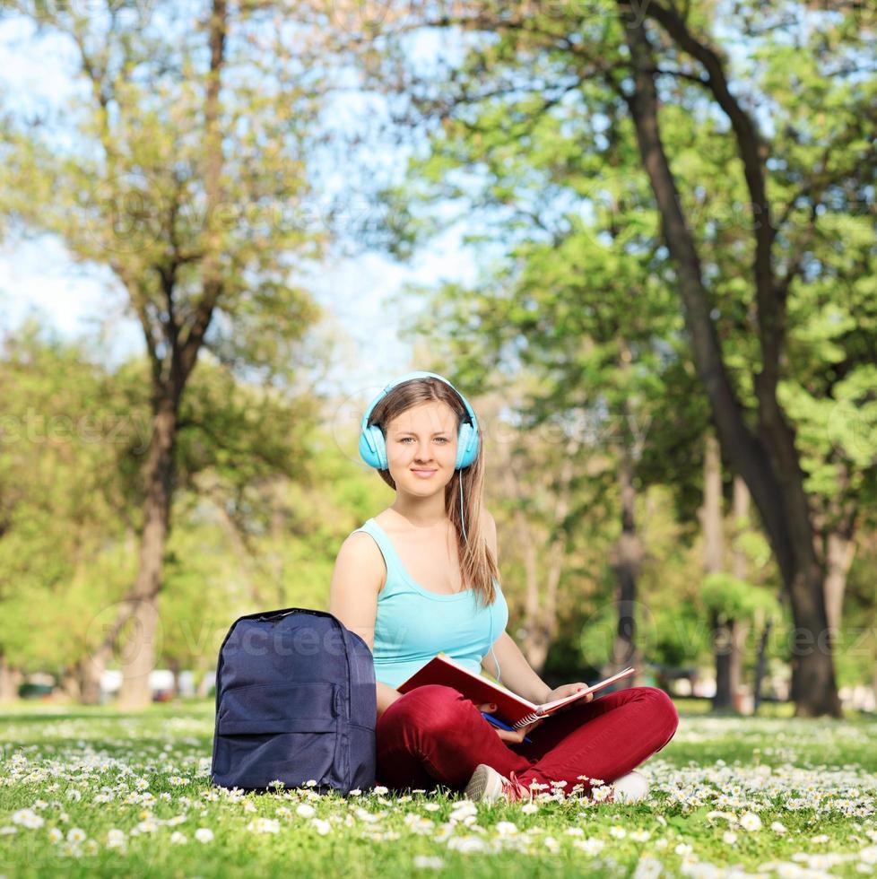 Studentin, die ein Buch im Park liest foto