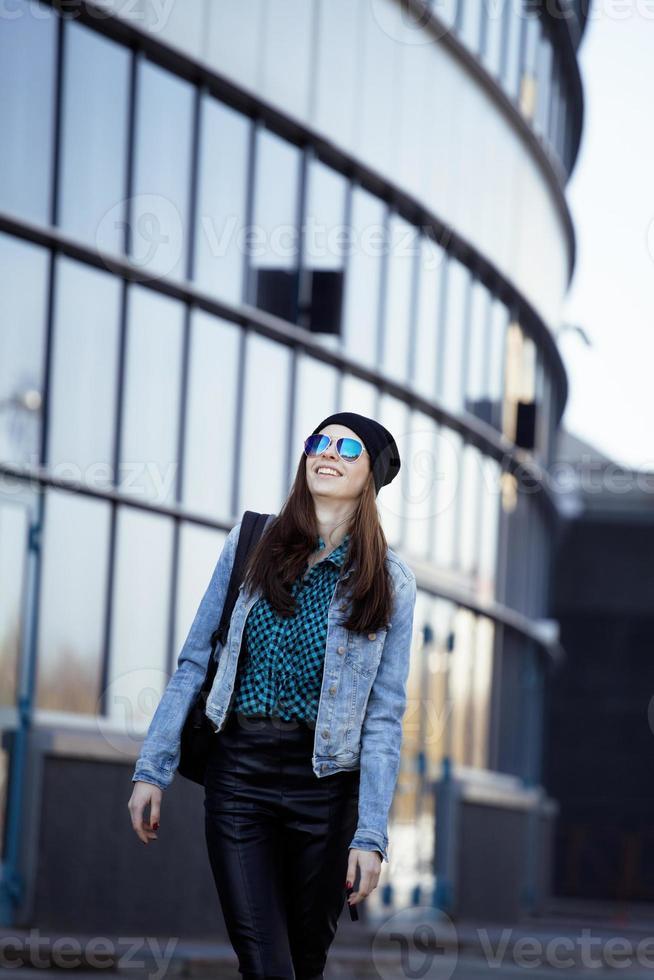 junges hübsches Mädchen in der Nähe des Geschäftsgebäudes zu Fuß, Student in Ame foto