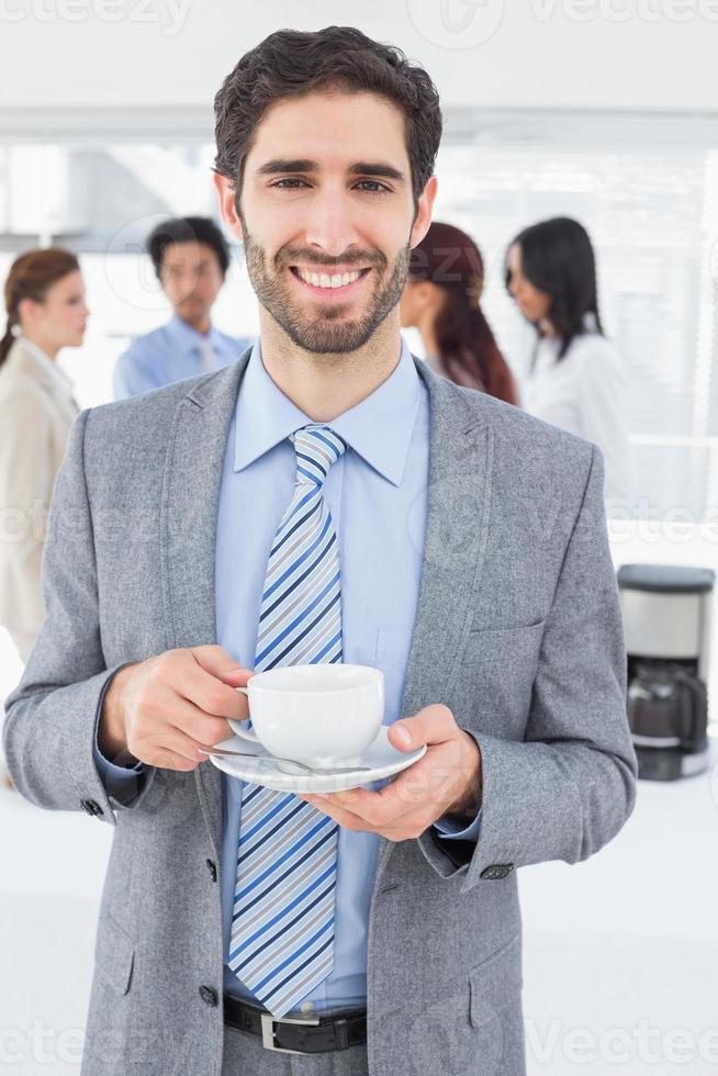 lächelnder Geschäftsmann mit einem Getränk foto