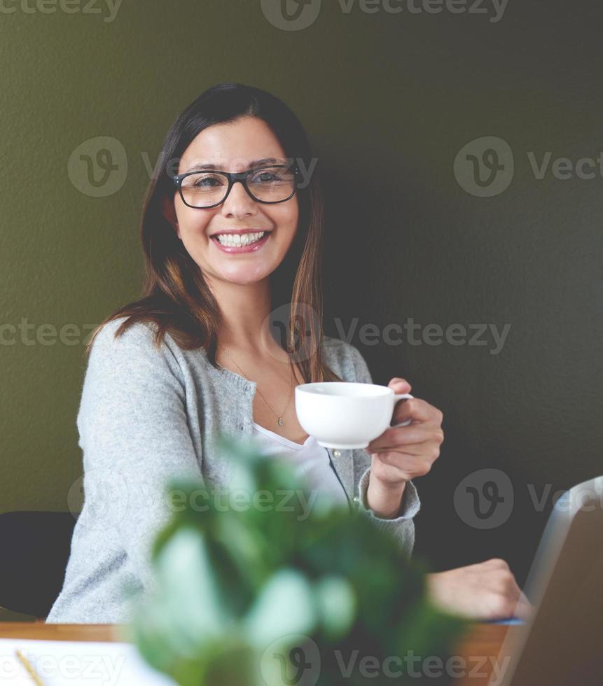 Frau lächelt und trinkt Kaffee. foto