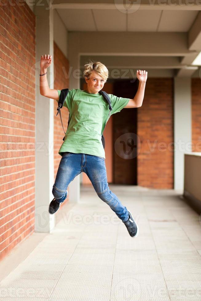 glücklicher männlicher Schüler springt foto
