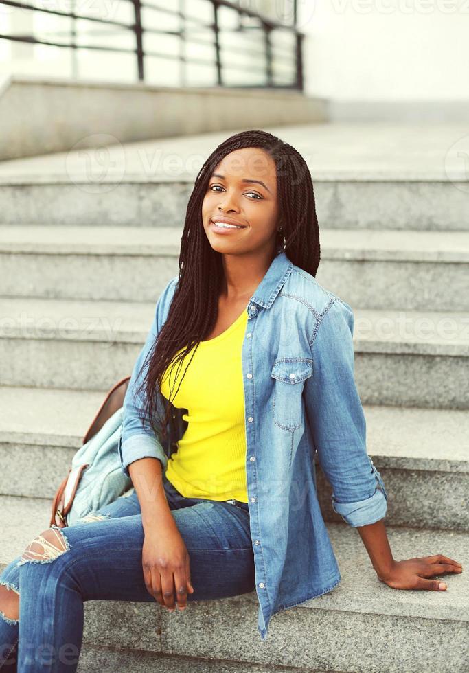 schöne glückliche lächelnde afrikanische Frau, die ein Jeanshemd sitzt sitt foto