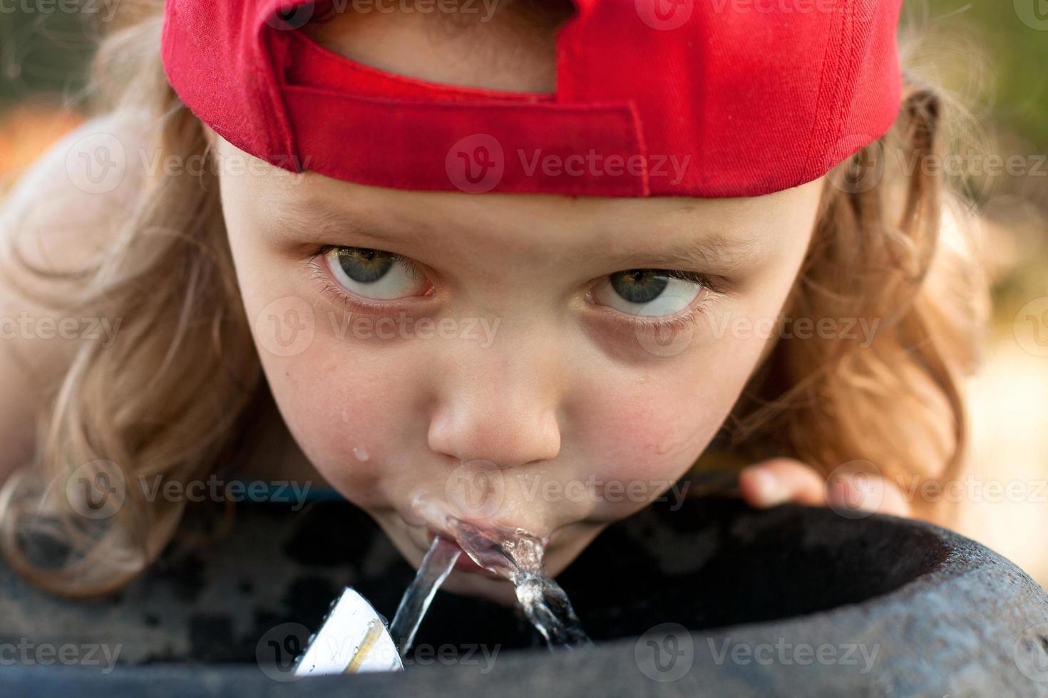 Kind trinkt aus Wasserbrunnen foto