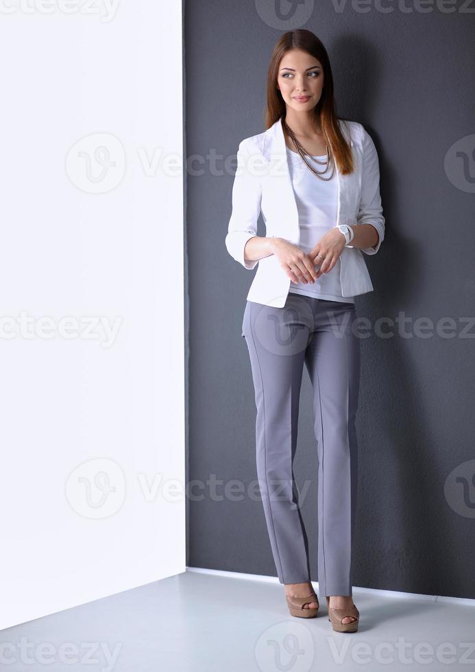 Doktorfrau mit Stethoskop lokalisiert auf grauem Hintergrund foto