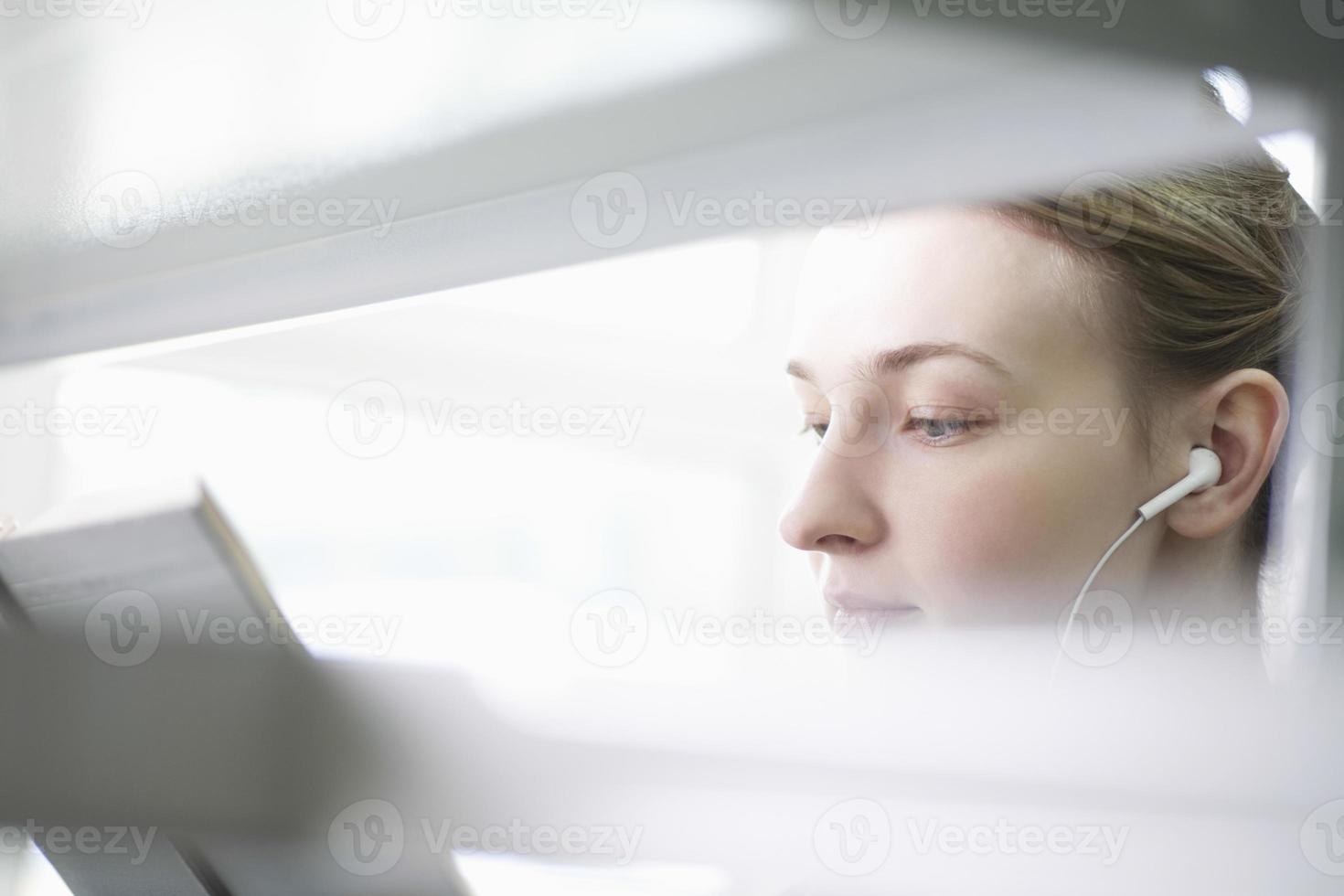 Frau, die Buch liest, während sie Musik hört foto