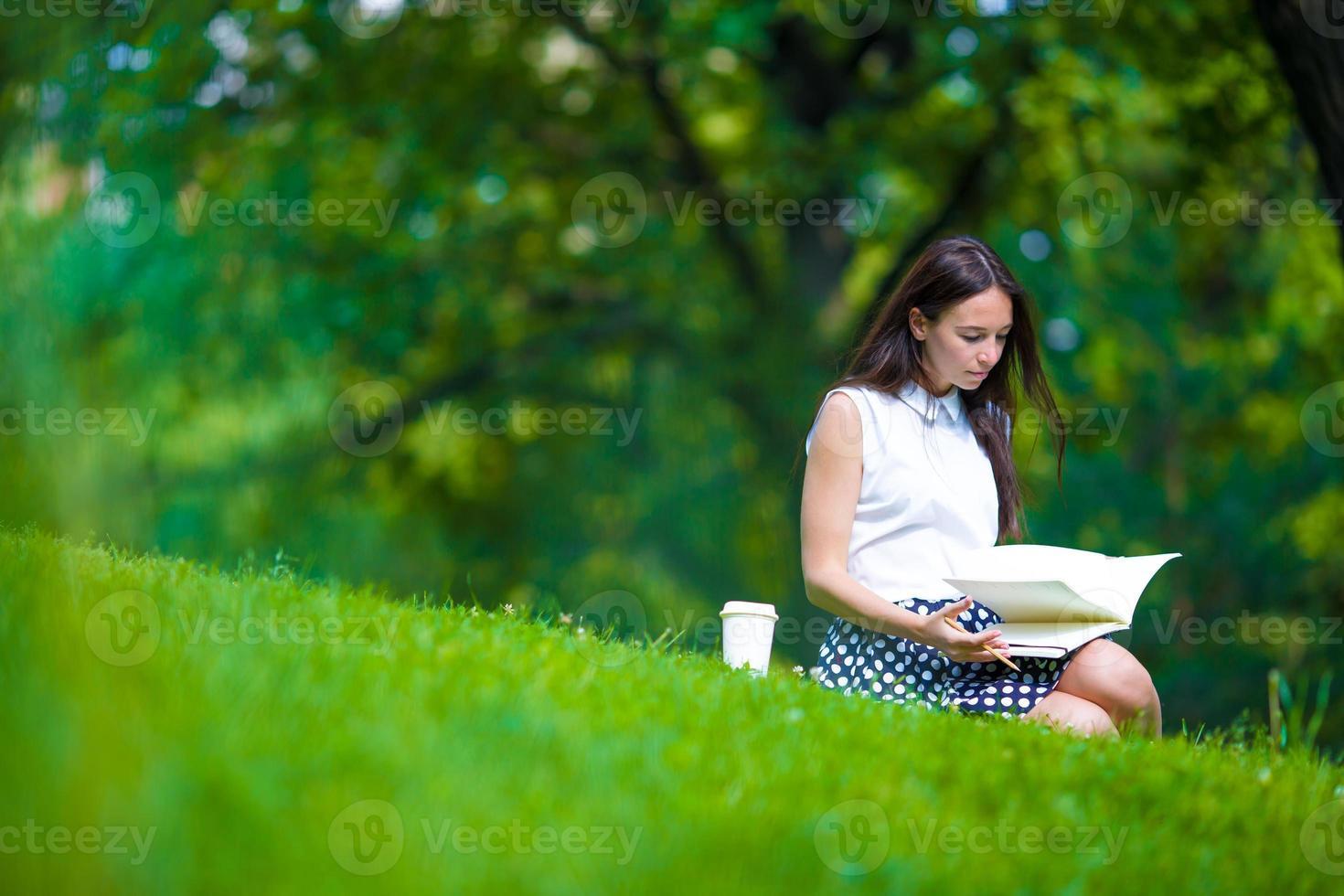 junge Frau, die mit Kaffee im Park entspannt, der ein Buch liest foto