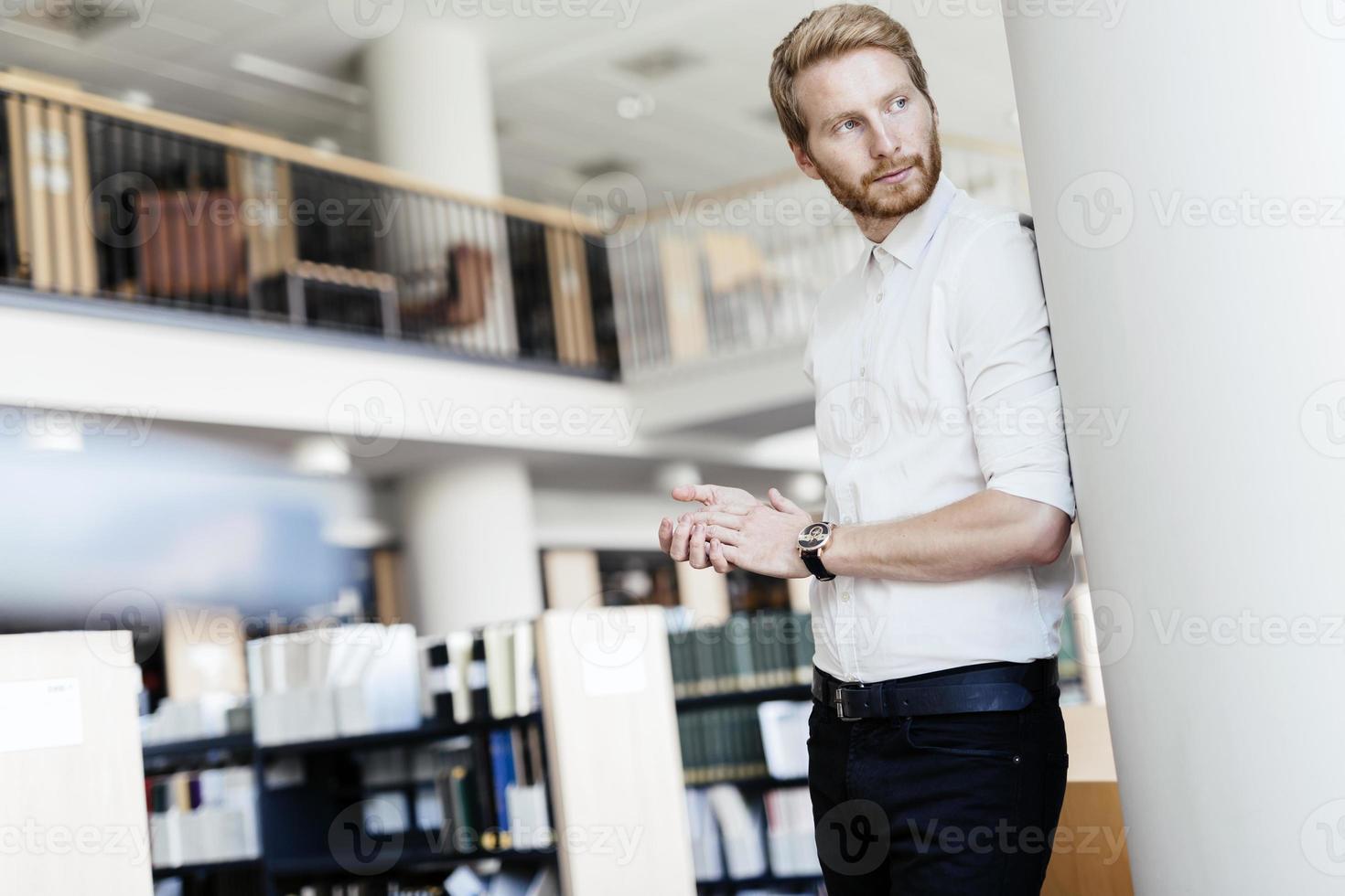 ernsthafter hübscher Student in der Bibliothek foto