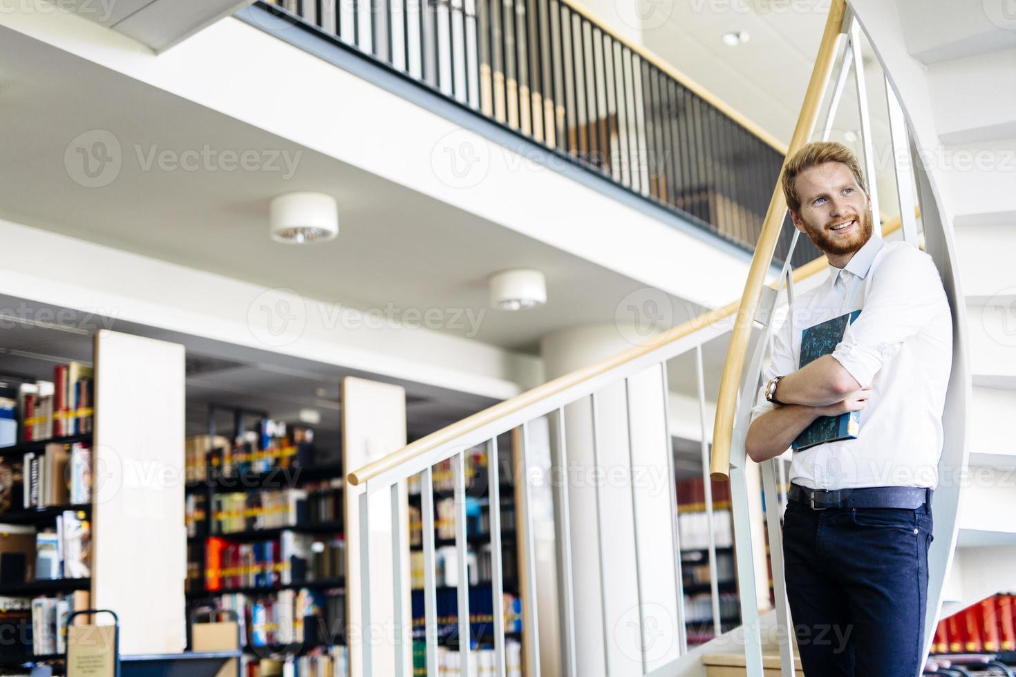 hübscher intelligenter Kerl, der ein Buch in einer Bibliothek liest foto