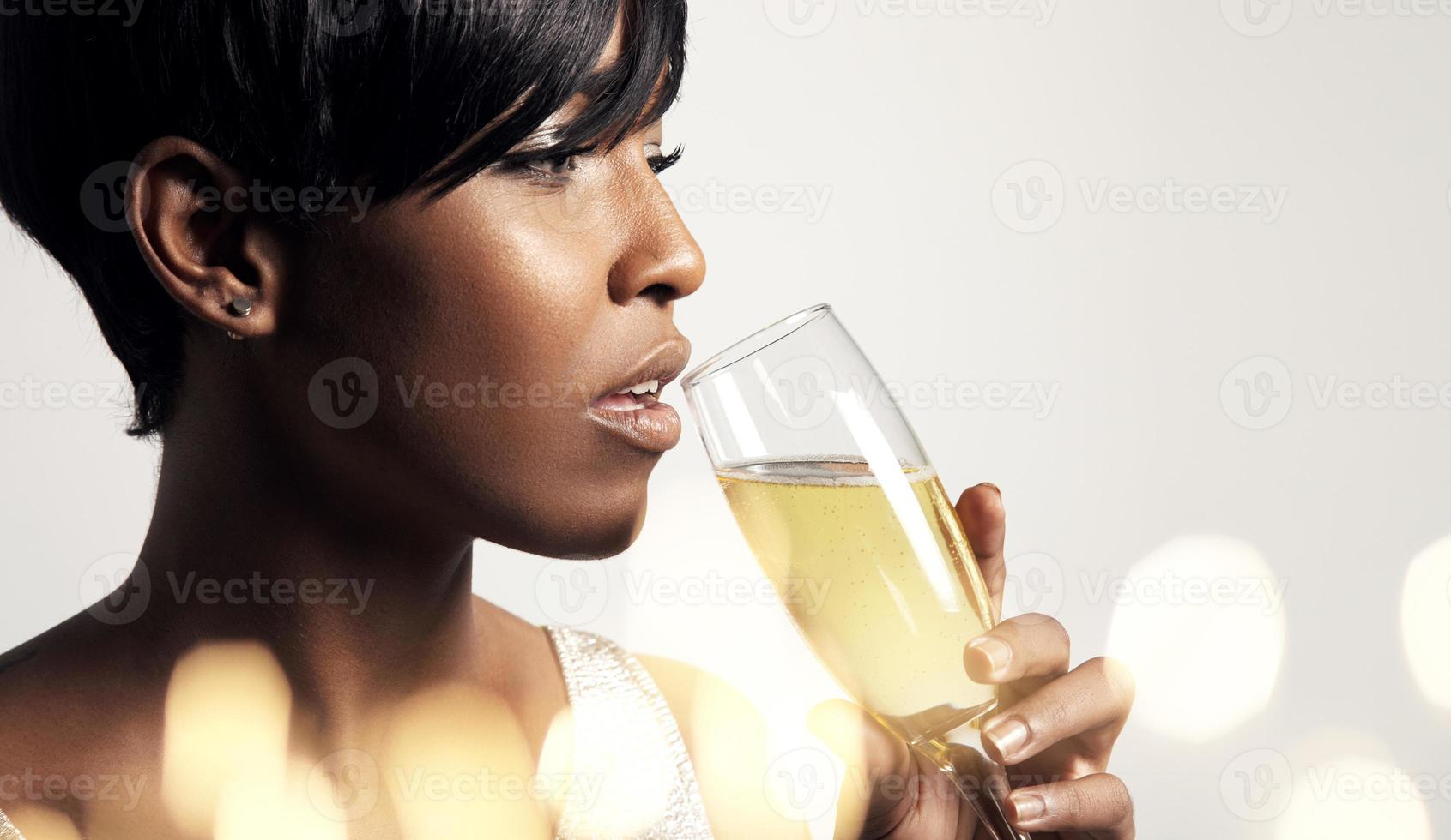 Frau trinkt aus Champagnerglas foto