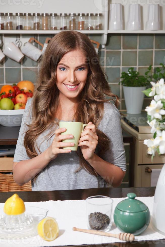 schöne glückliche Frau, die Tee trinkt foto