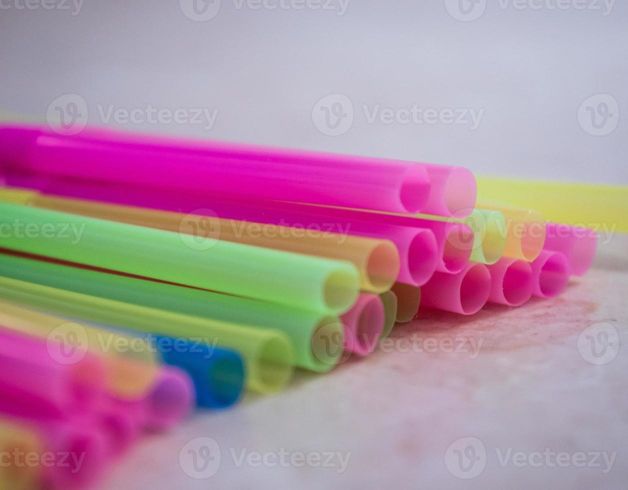gestapelte mehrfarbige Plastik-Trinkhalme foto