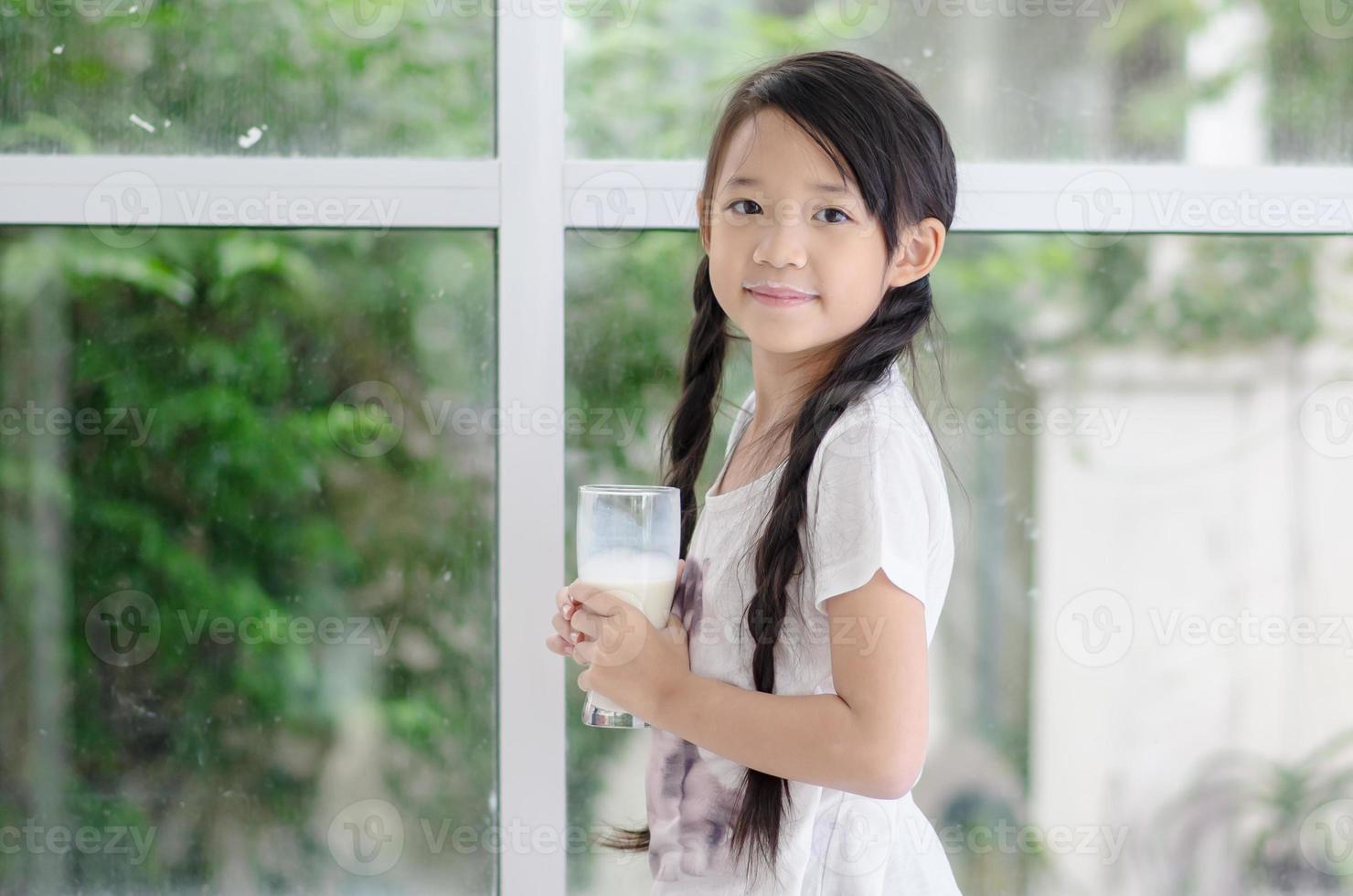kleines asiatisches Mädchen, das Milch trinkt foto