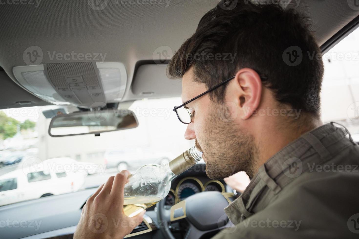 Mann trinkt Wein während der Fahrt foto