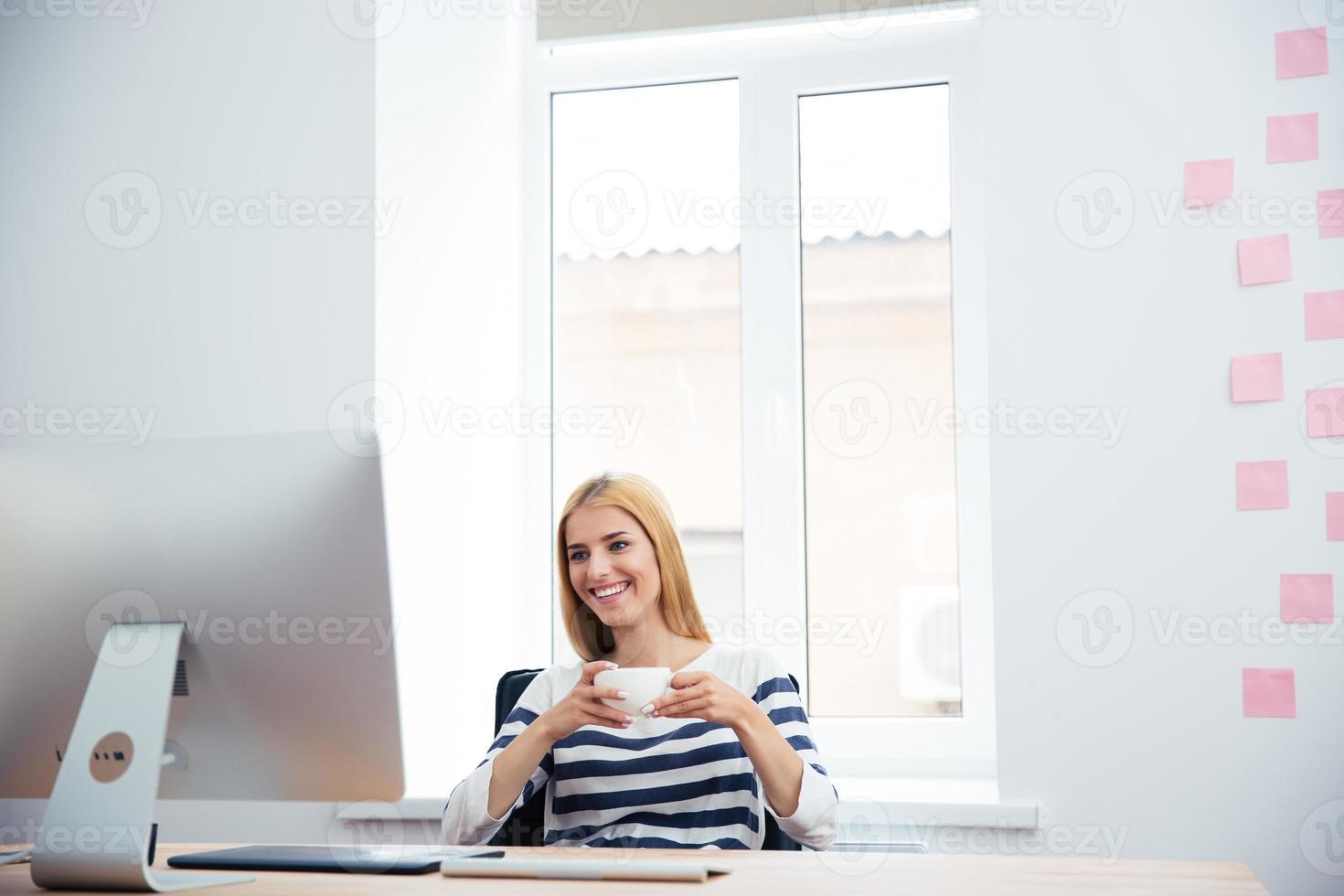 weiblicher Bildbearbeiter, der Kaffee trinkt foto