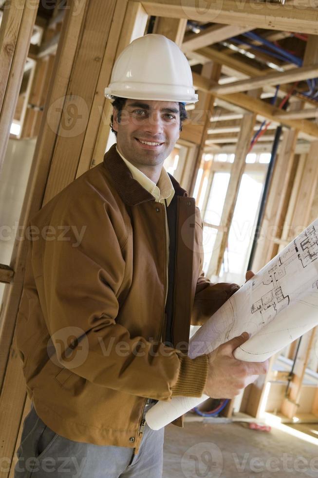 Mann hält Blaupause auf der Baustelle foto