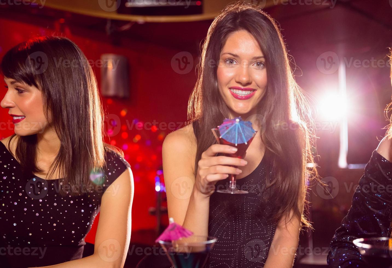 hübsche Brünette trinkt einen Cocktail foto