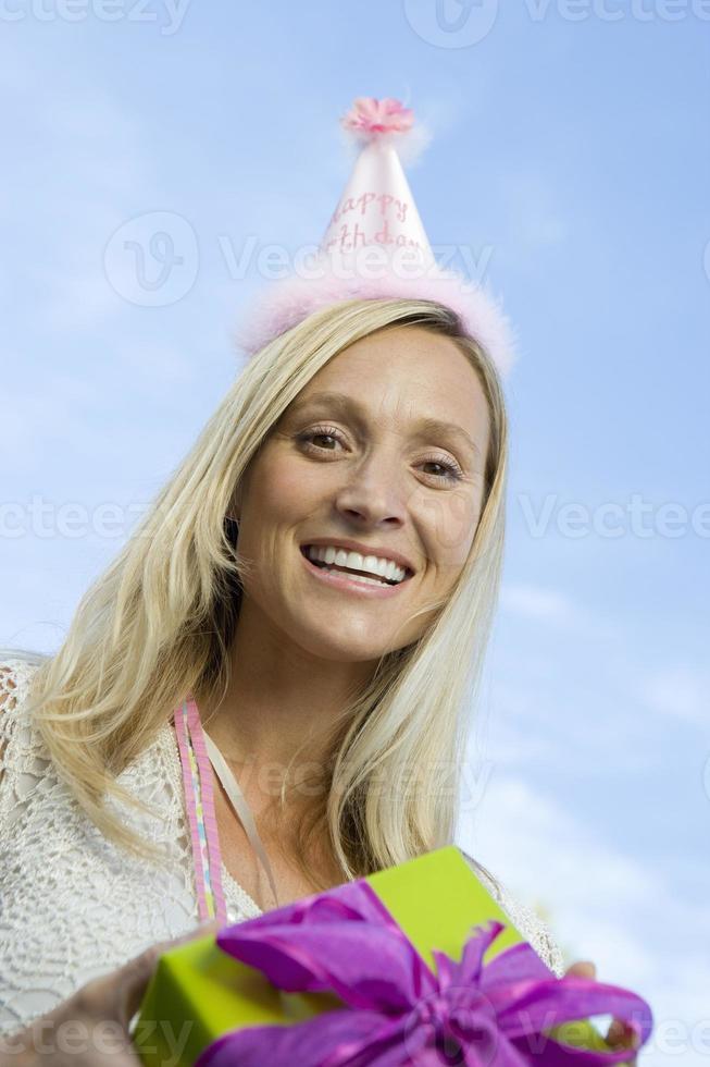 mittlere erwachsene Frau, die Geburtstagsgeschenk hält foto