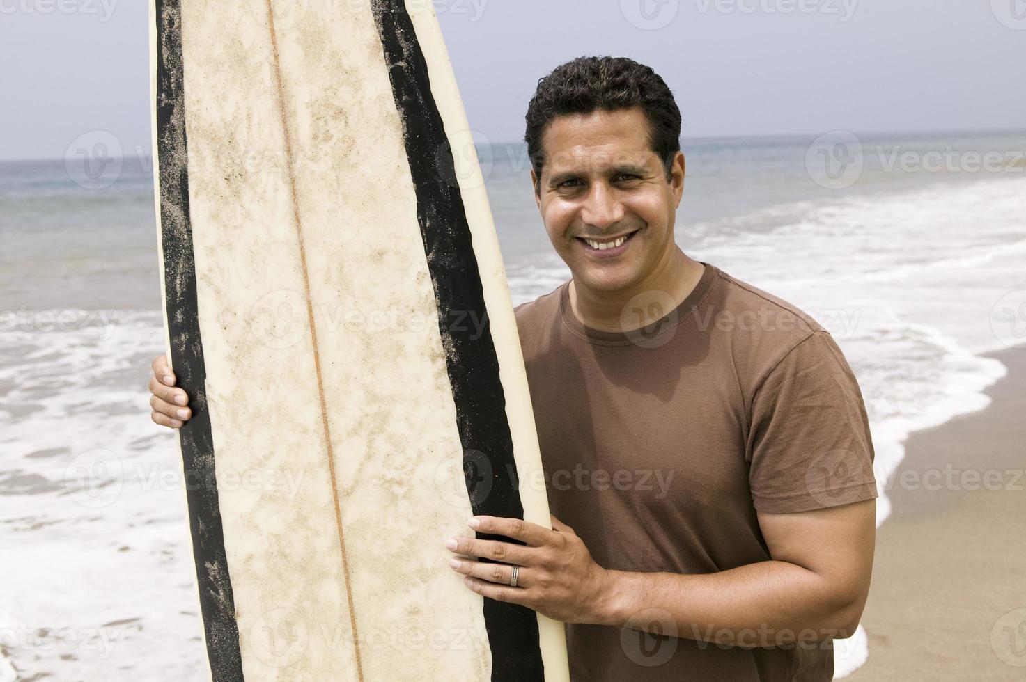 Porträt des Mannes, der Surfbrett am Strand hält foto