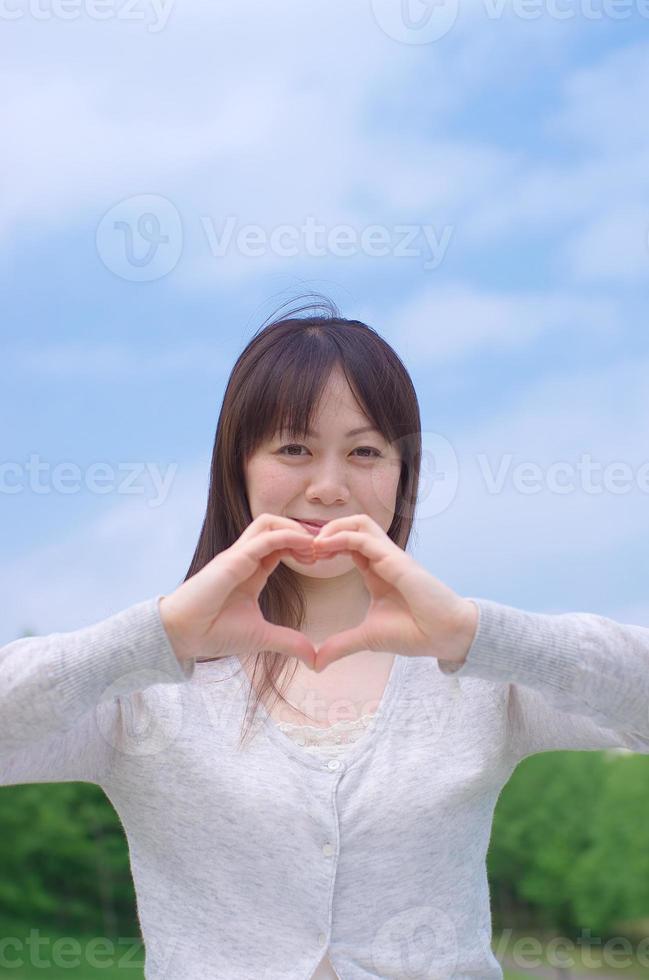asiatische Frau, die Herzform macht foto