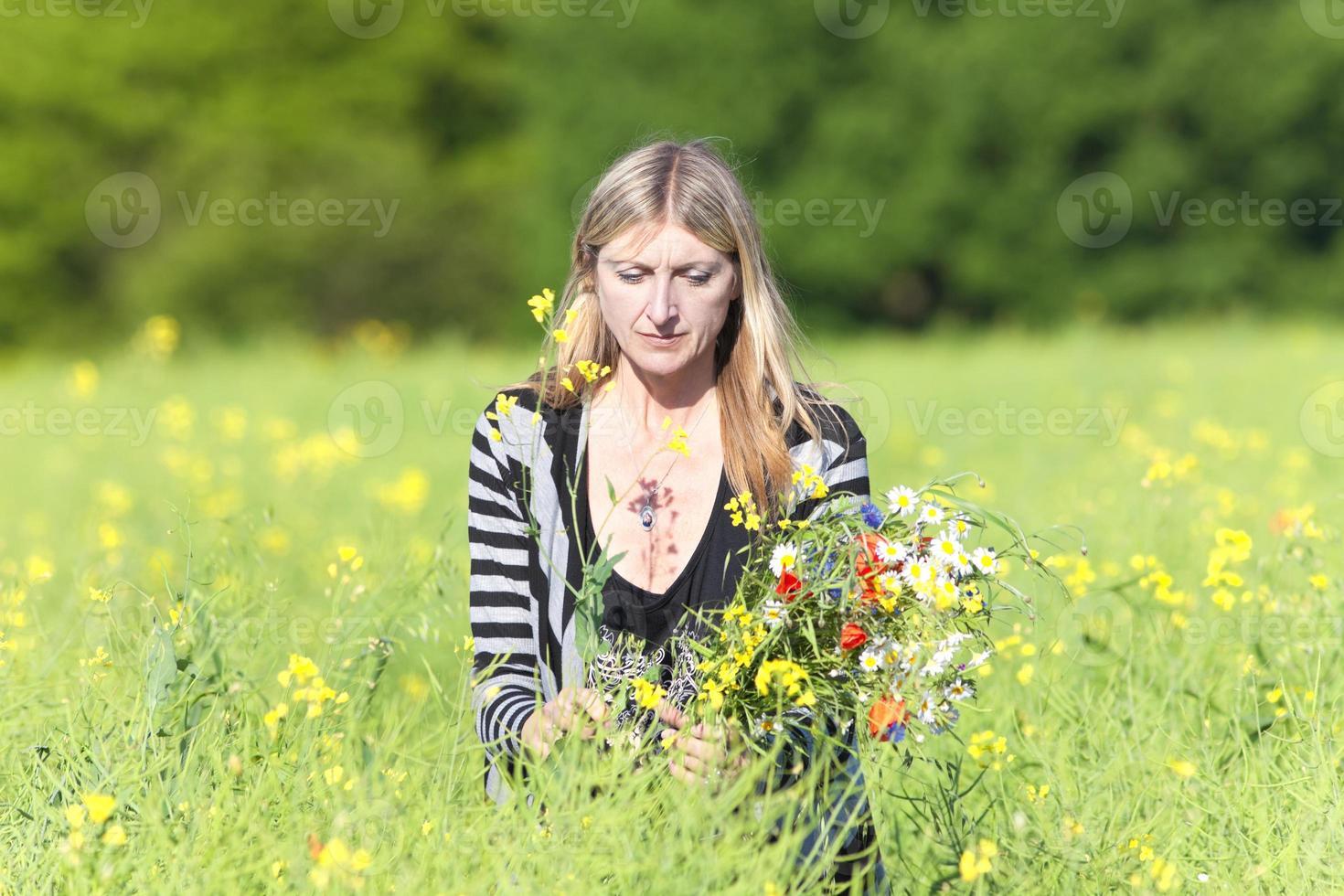 Frau, die wilde Blumen auf der Wiese pflückt foto