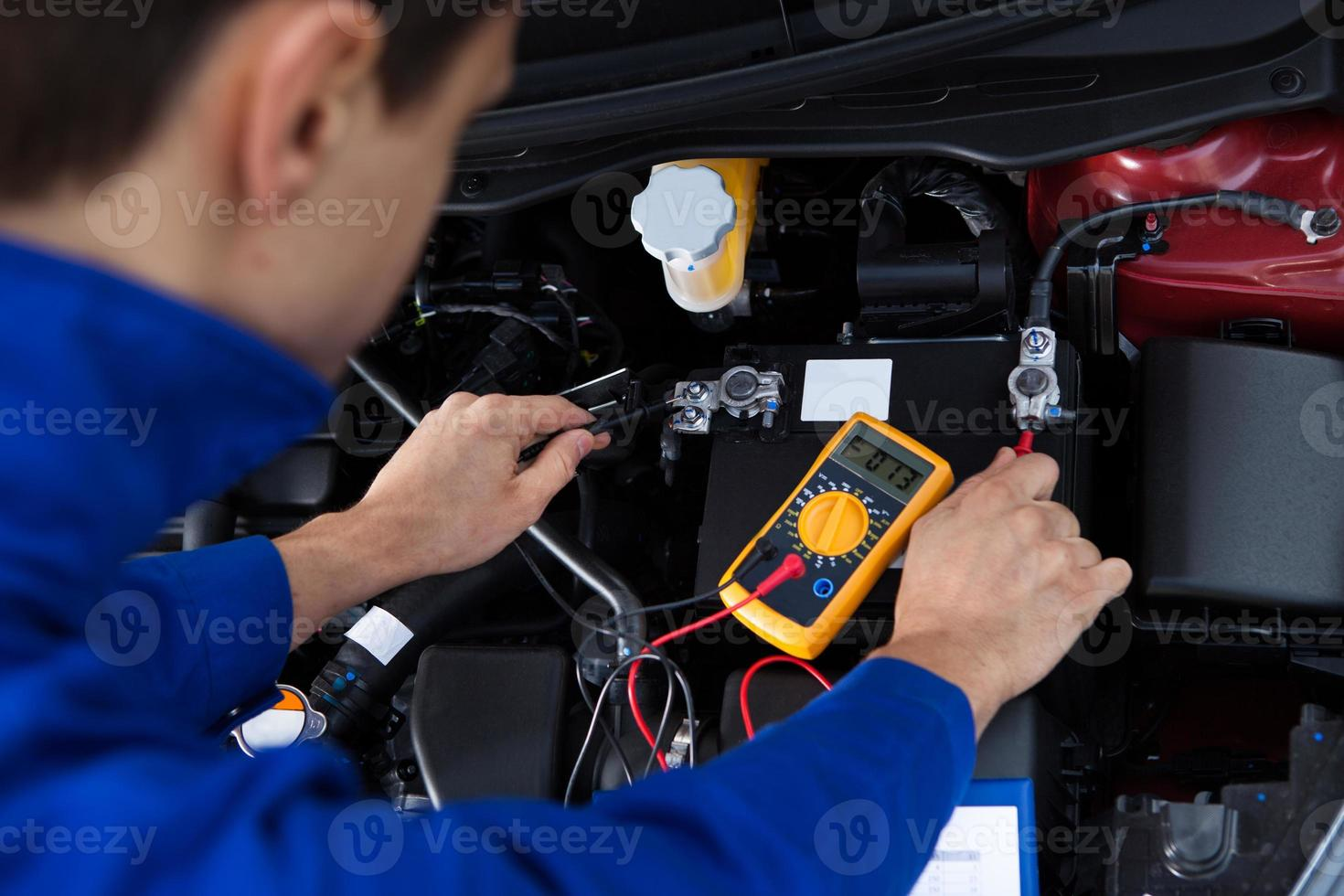 Mechaniker testet Autobatterie foto