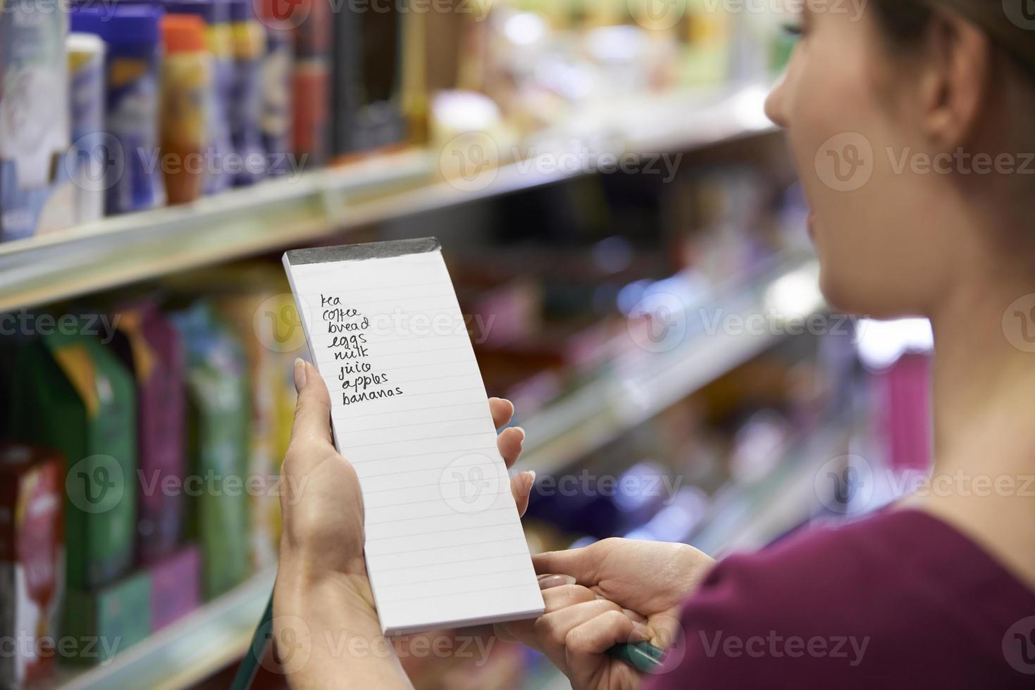 Frau liest Einkaufsliste im Supermarkt foto