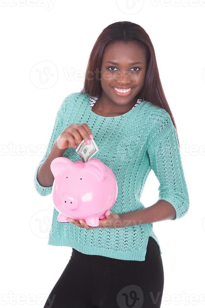 glückliche Frau, die Sparschwein hält foto