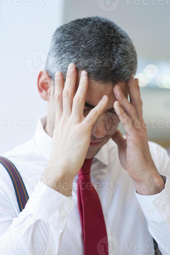 gestresster Geschäftsmann, der Hände zu Gesicht hält foto