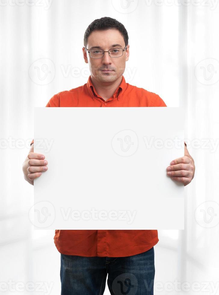 glücklicher junger Mann, der Plakat zeigt und anzeigt foto