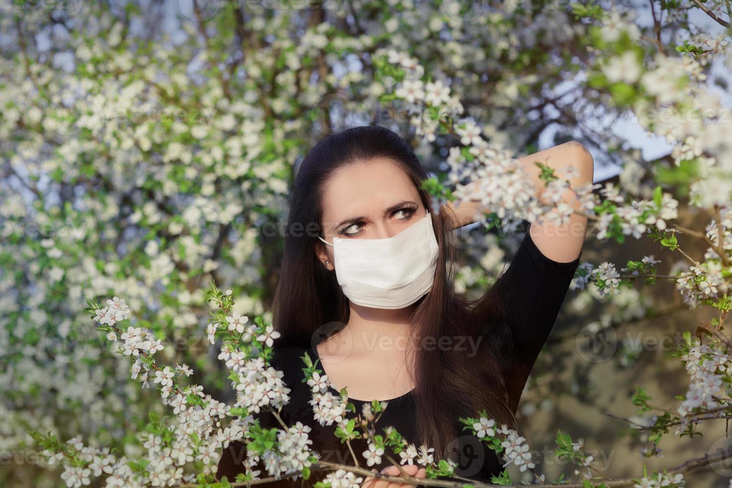 allergisches Mädchen mit Atemschutzmaske im blühenden Dekor des Frühlings foto