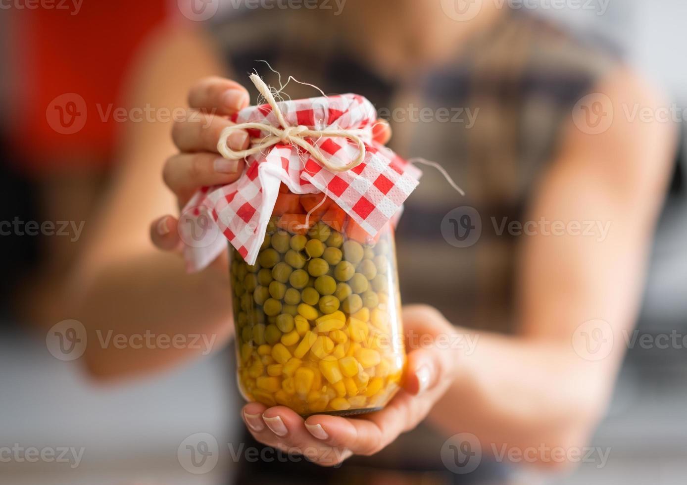 Nahaufnahme auf junge Hausfrau, die Glas mit eingelegtem Gemüse zeigt foto