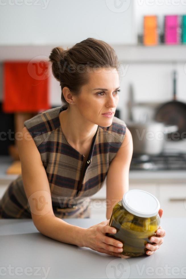 elegante Frau, die sich auf Küchentheke stützt und Glas der Gurken hält foto