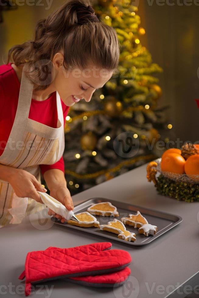 junge Hausfrau, die Weihnachtsplätzchen mit Spritzbeutel verziert foto
