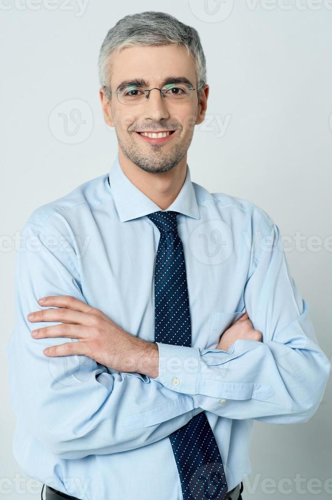 fröhlicher Geschäftsmann mit verschränkten Armen foto
