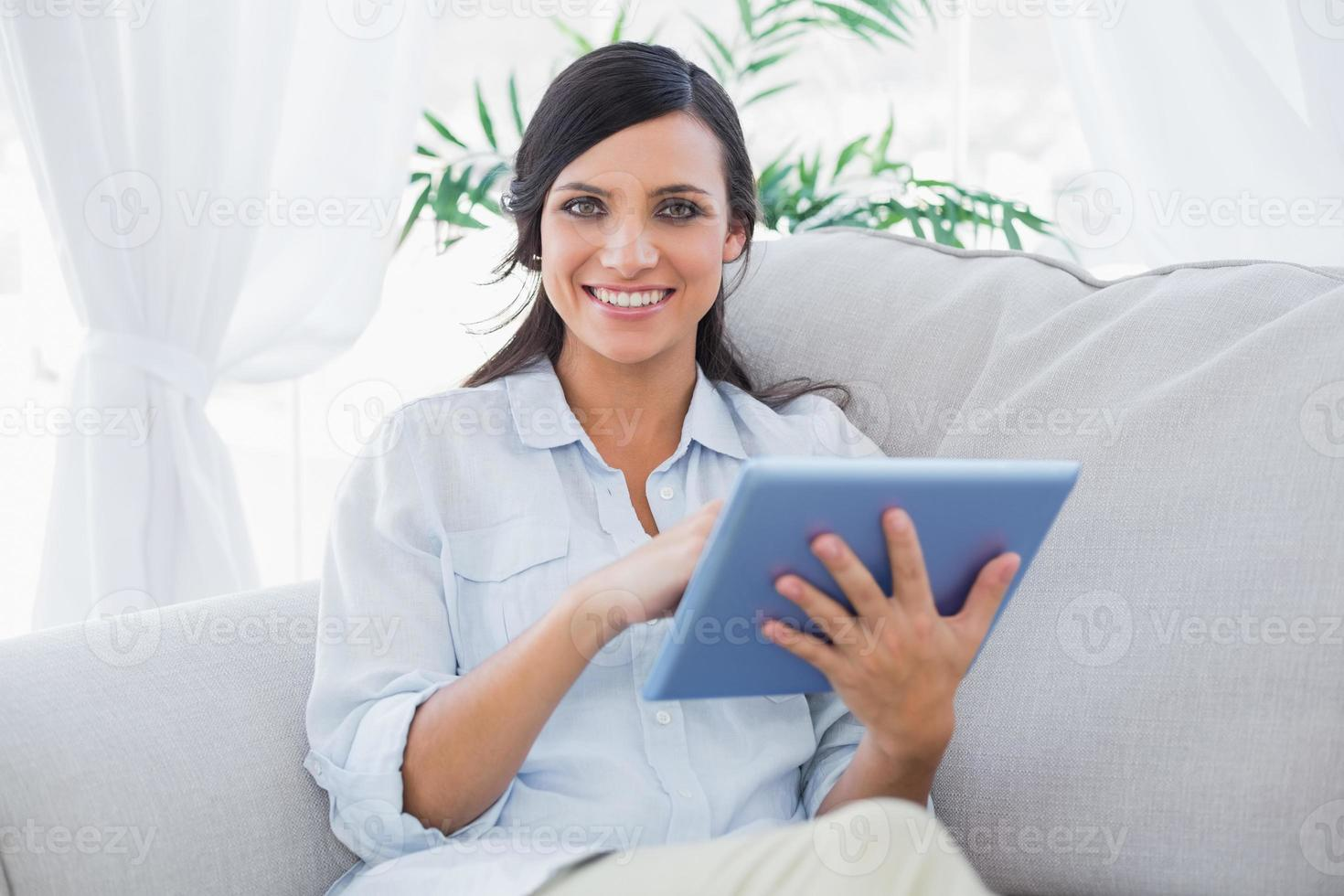 fröhliche Brünette mit Tablet-PC foto