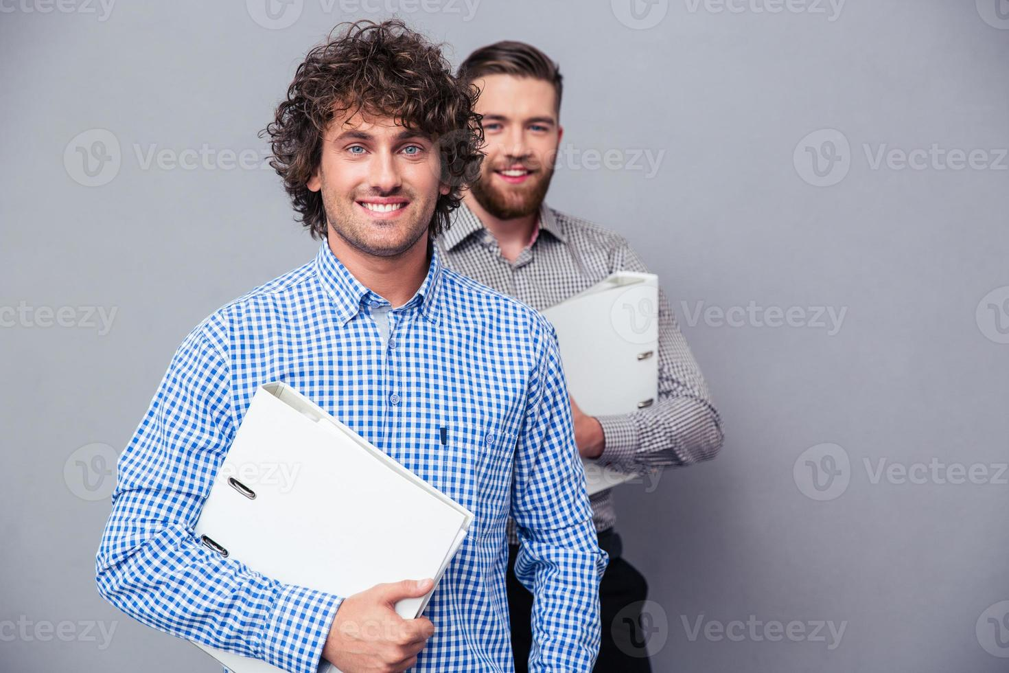 zwei fröhliche Geschäftsleute, die Ordner halten foto