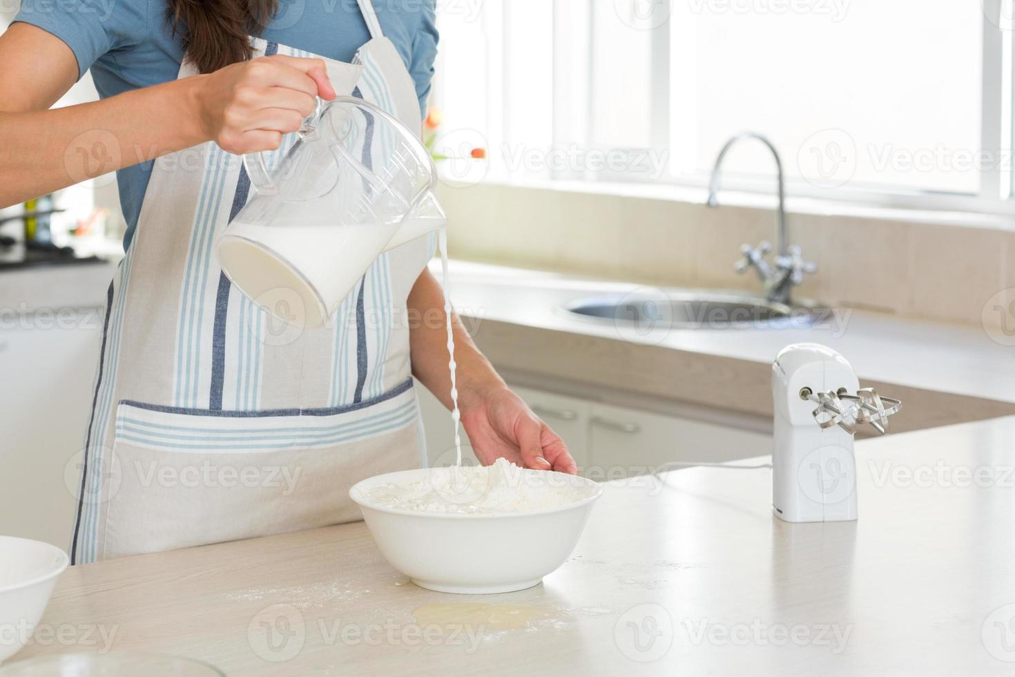 Mittelteil der Frau, die Milch in Teig in der Küche gießt foto