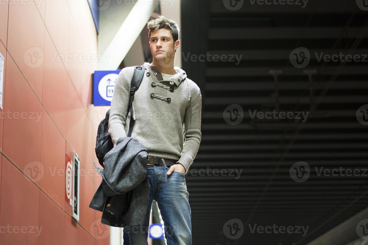 schöner junger Mann, der im Zug oder in der U-Bahnstation steht foto
