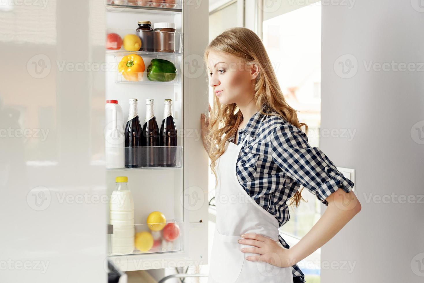 Frau mit offenem Kühlschrank foto