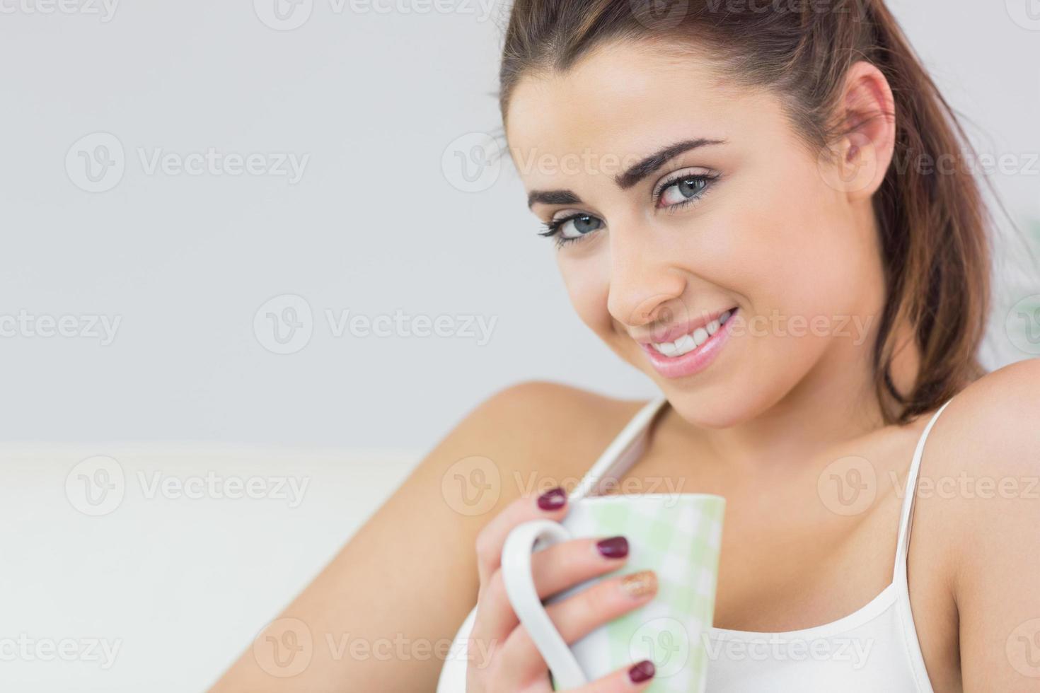 fröhliche junge Frau, die eine Tasse hält foto