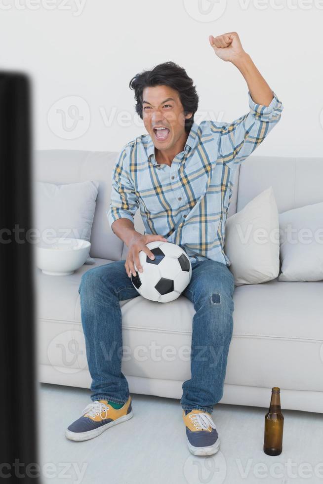 Fußballfan jubelt beim Fernsehen foto