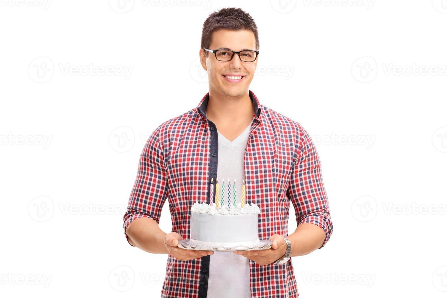 fröhlicher junger Mann, der eine Geburtstagstorte hält foto