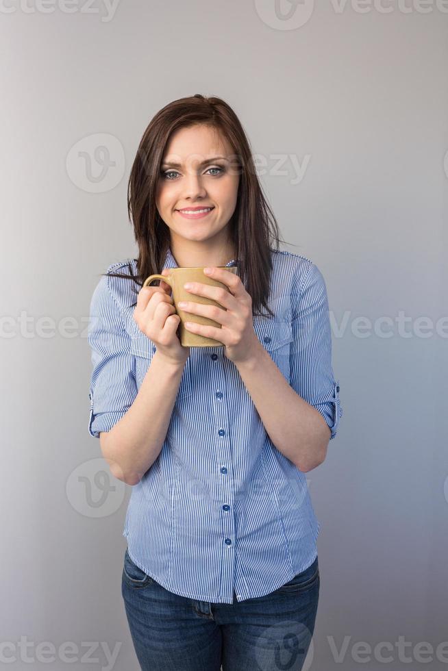 fröhliche hübsche Brünette, die Tasse Kaffee hält foto